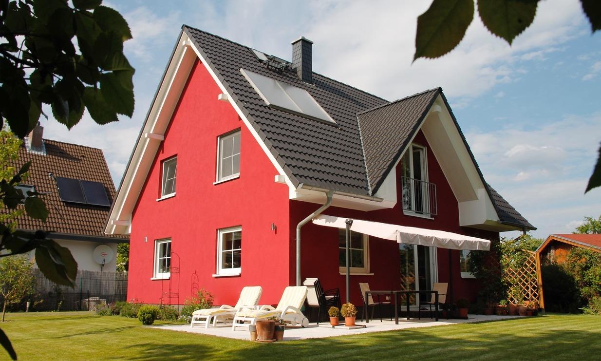 Einfamilienhaus mit roter Fassade und noch einfacher Rasenfläche