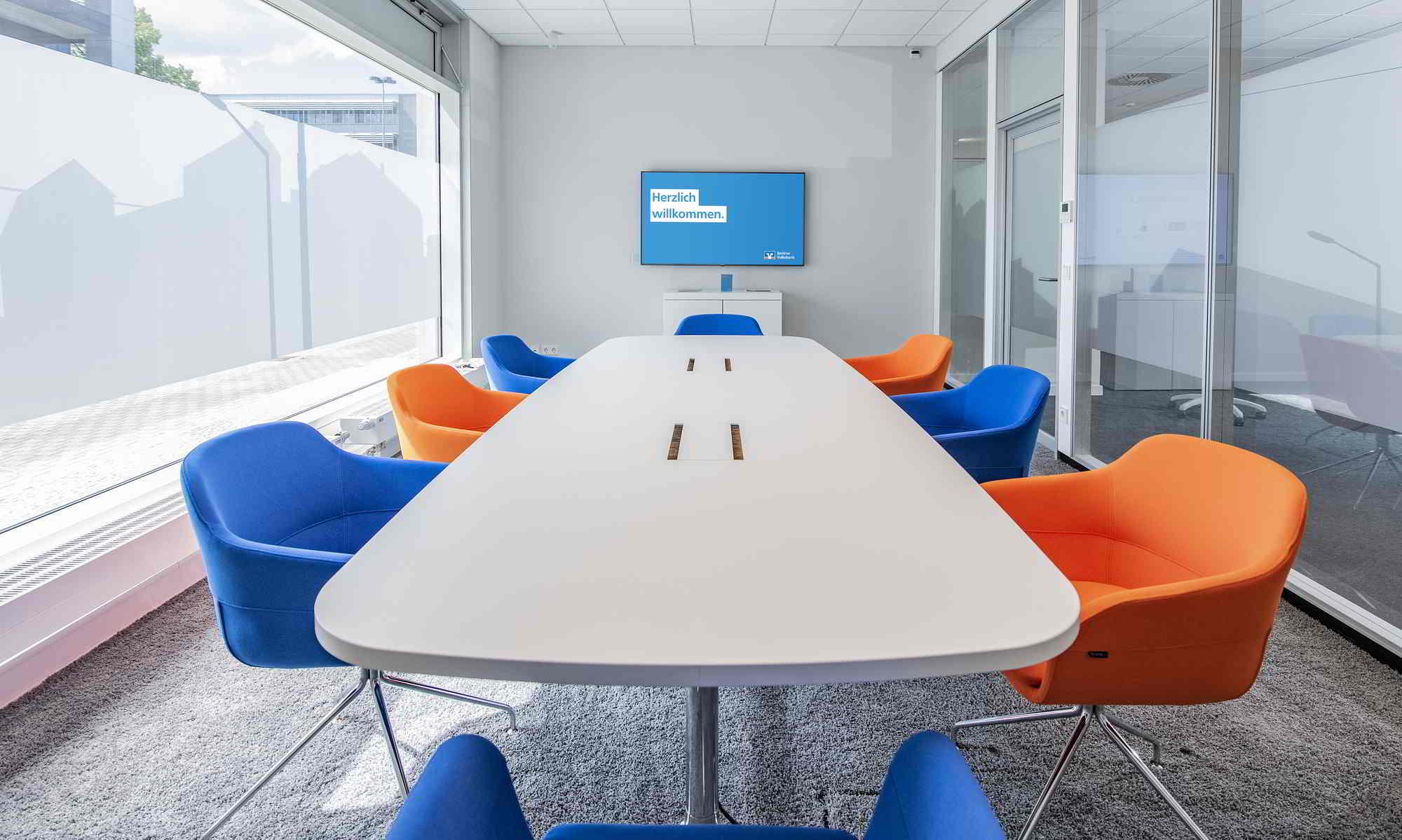 Weißer Konferenztisch mit Stühlen in den Volksbankfarben: orange und blau