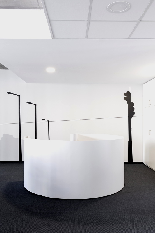 Das obere Ende der Wendeltreppe: Eine weiße runde Fläche mit einer vom Betrachter abgewandten Öffnung