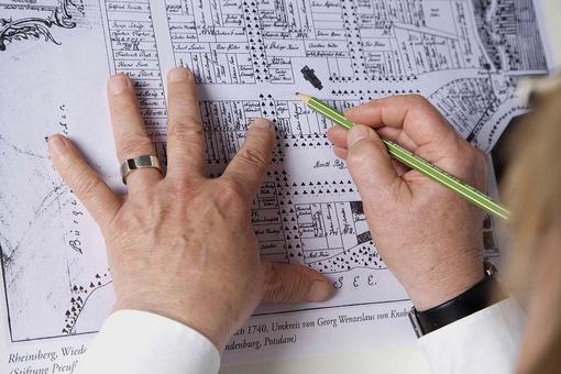 Blick über die Schulter: Hände auf einem historischen Stadtplan