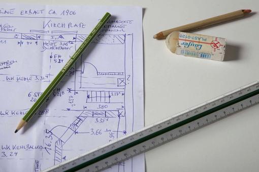 zwei Stifte, ein Lineal und ein Radiergummi liegen auf einem skizzierten Hausgrundriss
